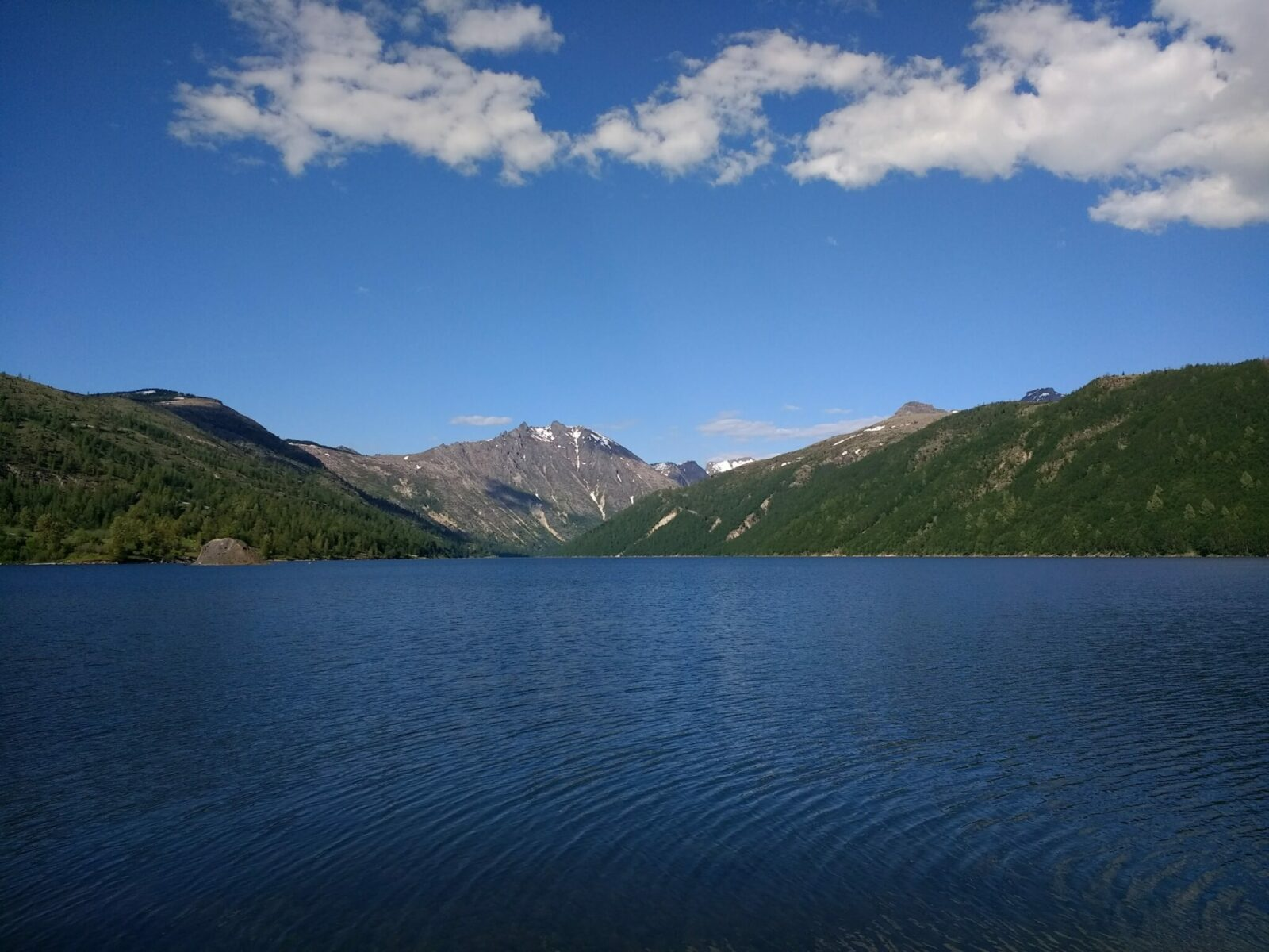 A blue lake surrounded by forested hillsides and mountains
