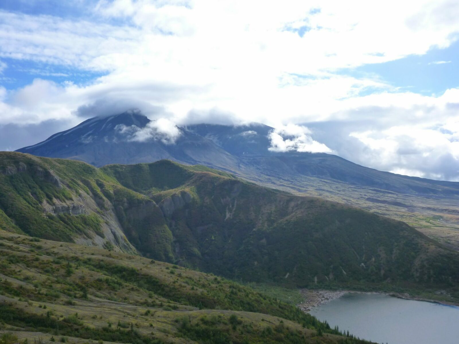 Forested and shrub covered hillsides above a lake with the crater of Mt St Helens in the distance, partially covered by clouds