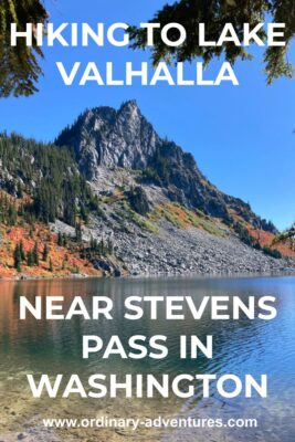 An alpine lake and a rocky mountain on the opposite side of the lake. There are evergreen trees, gray rocks and bright orange and red berry bushes in fall color around the mountain across the lake. Text reads: hiking to lake valhalla near stevens pass washington