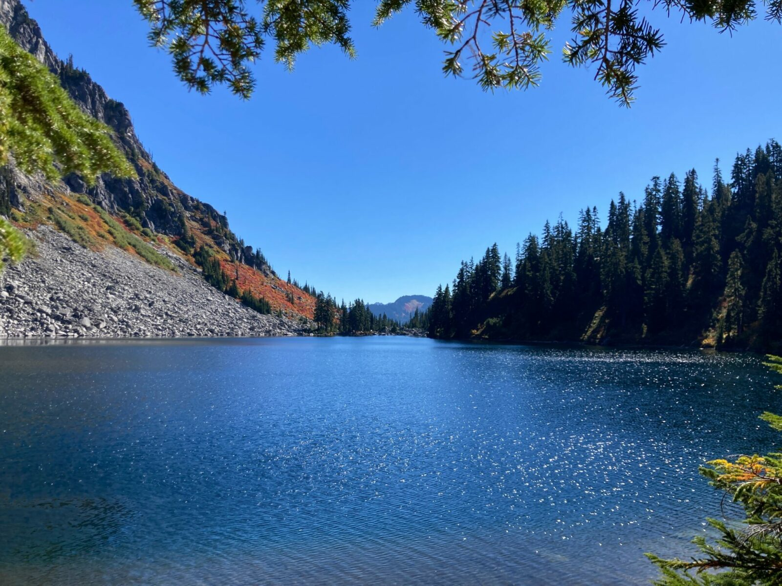 Lake Valhalla on a sunny day, surrounded by evergreen trees and gray rocks.