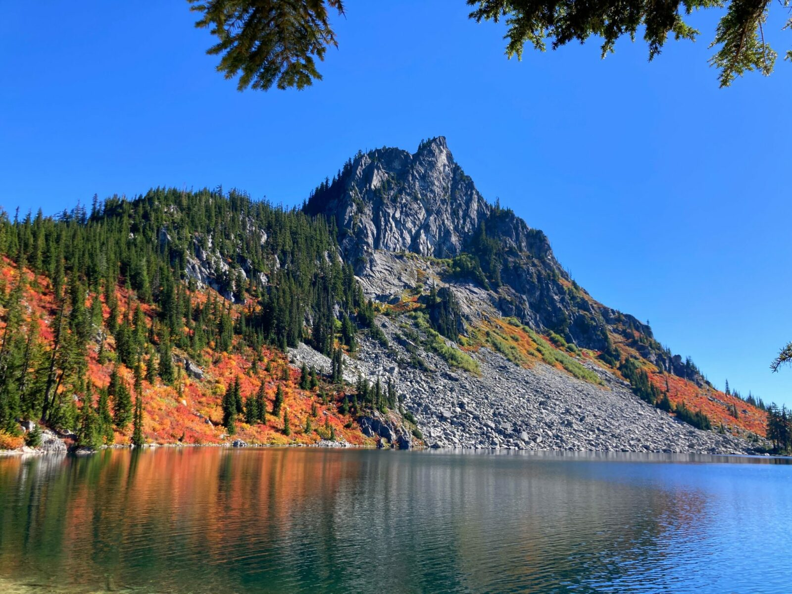 Calm, alpine Lake Valhalla with a rocky mountain on the opposite side of the lake. There are evergreen trees, gray rocks and bright orange and red berry bushes in fall color around the mountain across the lake