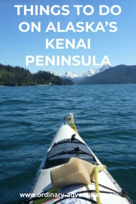 The front of a white kayak from the perspective of the person paddling it. In the distance are high snow capped mountains and evergreen forested hillsides. Text reads: things to do on alaska's kenai peninsula