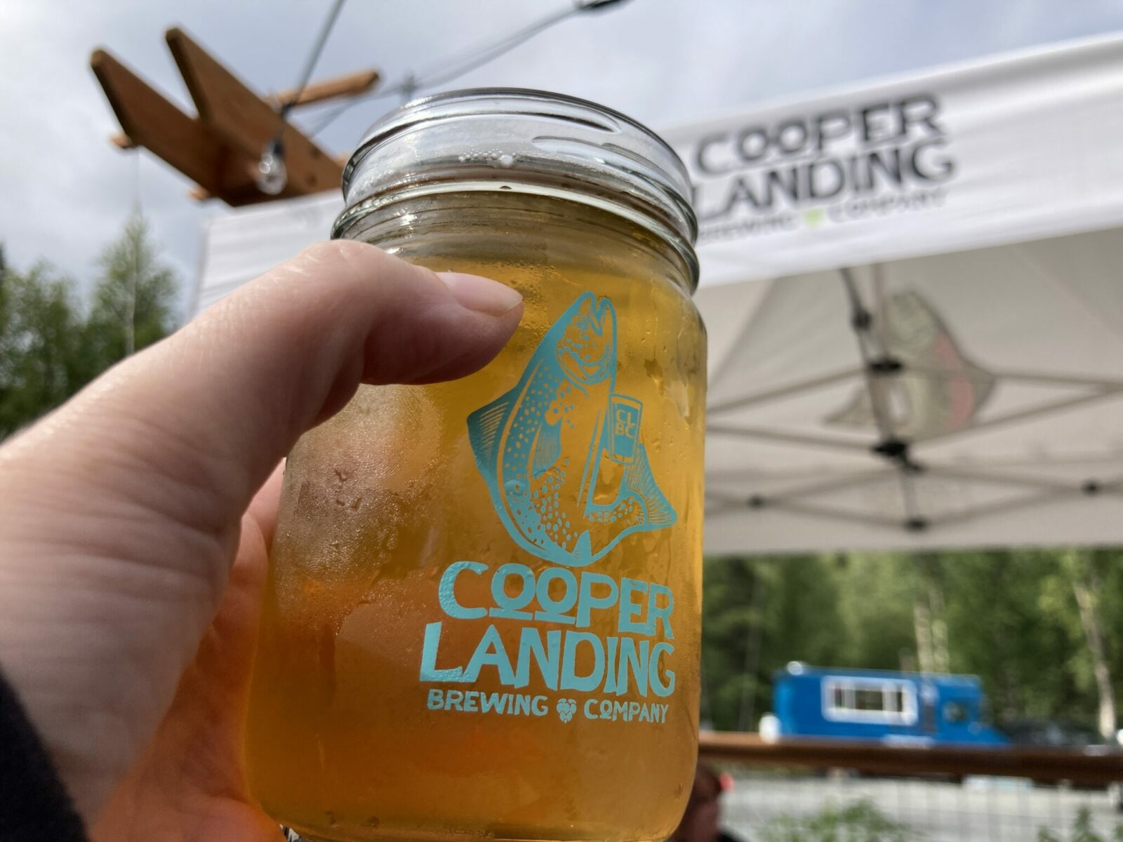 """a glass jar with beer in it that says """"cooper landing brewing company"""" with a picture of a salmon. A person's hand is holding the beer"""