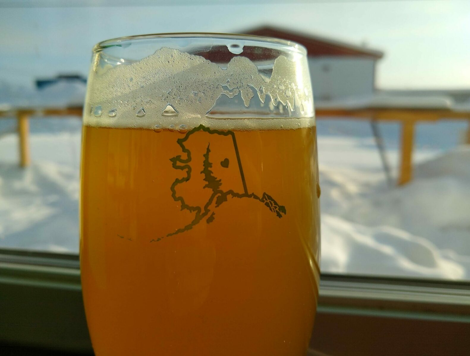 a beer in a glass next to a window with snow outside at a brewery in alaska. The glass has the outine of the shape of the state of alaska