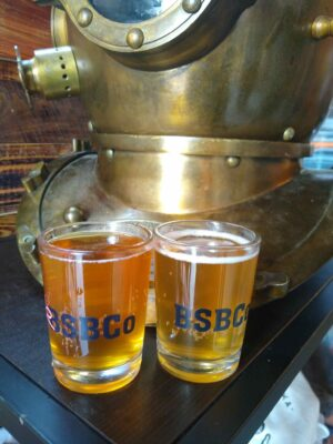 Two small beer tasting glasses filled with beer with the initials BSBC, one of the breweries in Alaska