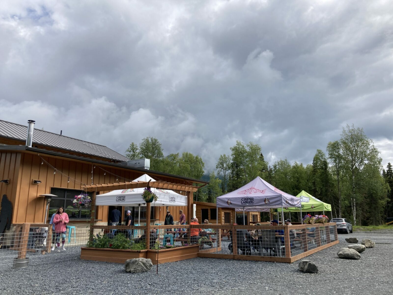 A fence with tables and tents over the tables at one of the breweries in Alaska. There is a large brown building and trees around a gravel parking lot next to the tents