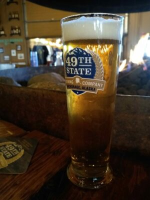A glass of beer on a bar. The glass says 49th State brewing company, Anchorage Alaska, one of the breweries in Alaska