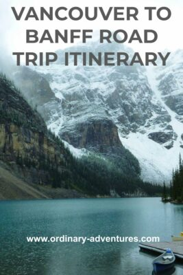 A turquoise mountain lake with high mountains with fresh snow and forest surrounding the lake and a canoe at the edge of the lake. Text reads: Vancouver to Banff Road trip itinerary