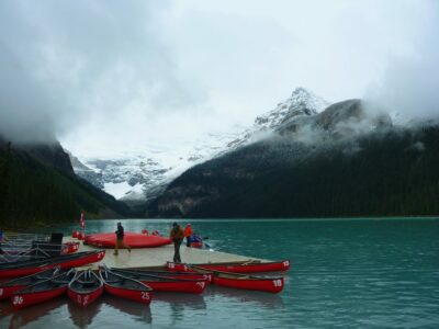 A dock with several bright red canoes in turquoise water at Lake Louise between Vancouver and banff. There are high mountains with fresh snow around the lake that are partially covered by clouds