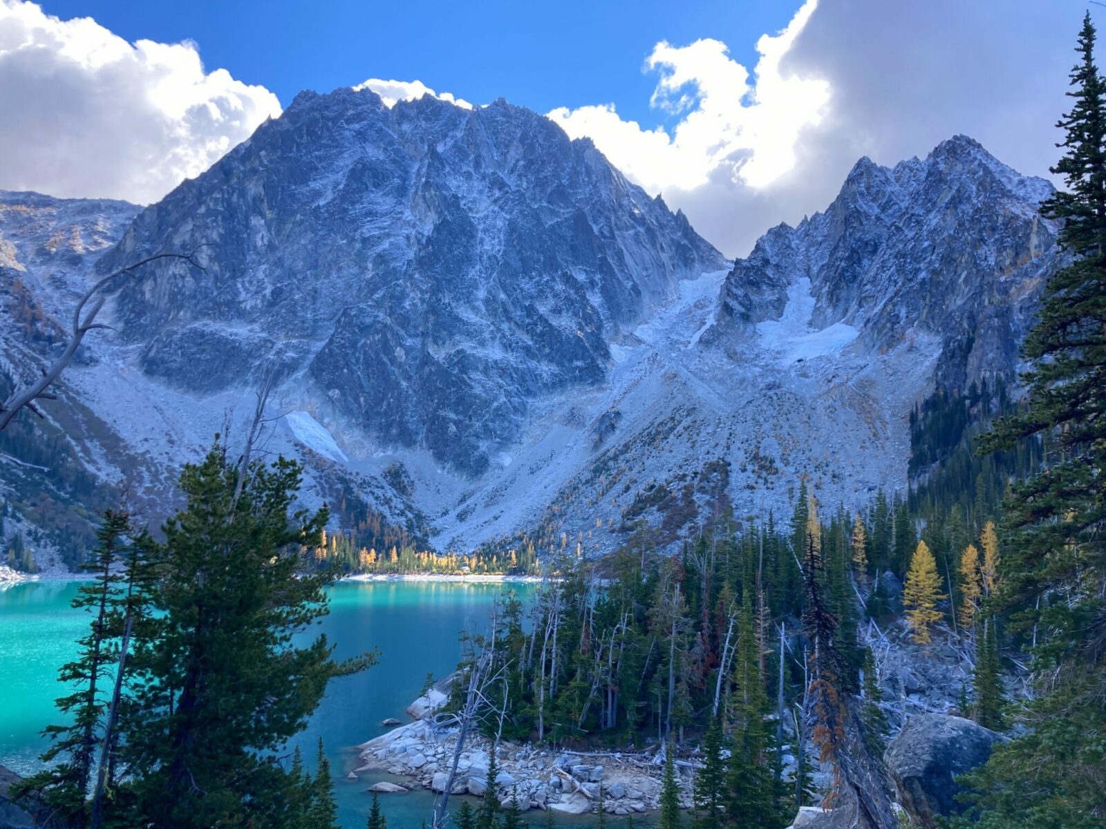 Colchuck Lake is a turquoise blue alpine lake surrounded by granite rock formations and subalpine firs. There are high mountains around it with a dusting of new snow, some golden larch trees and two glaciers hanging between mountains