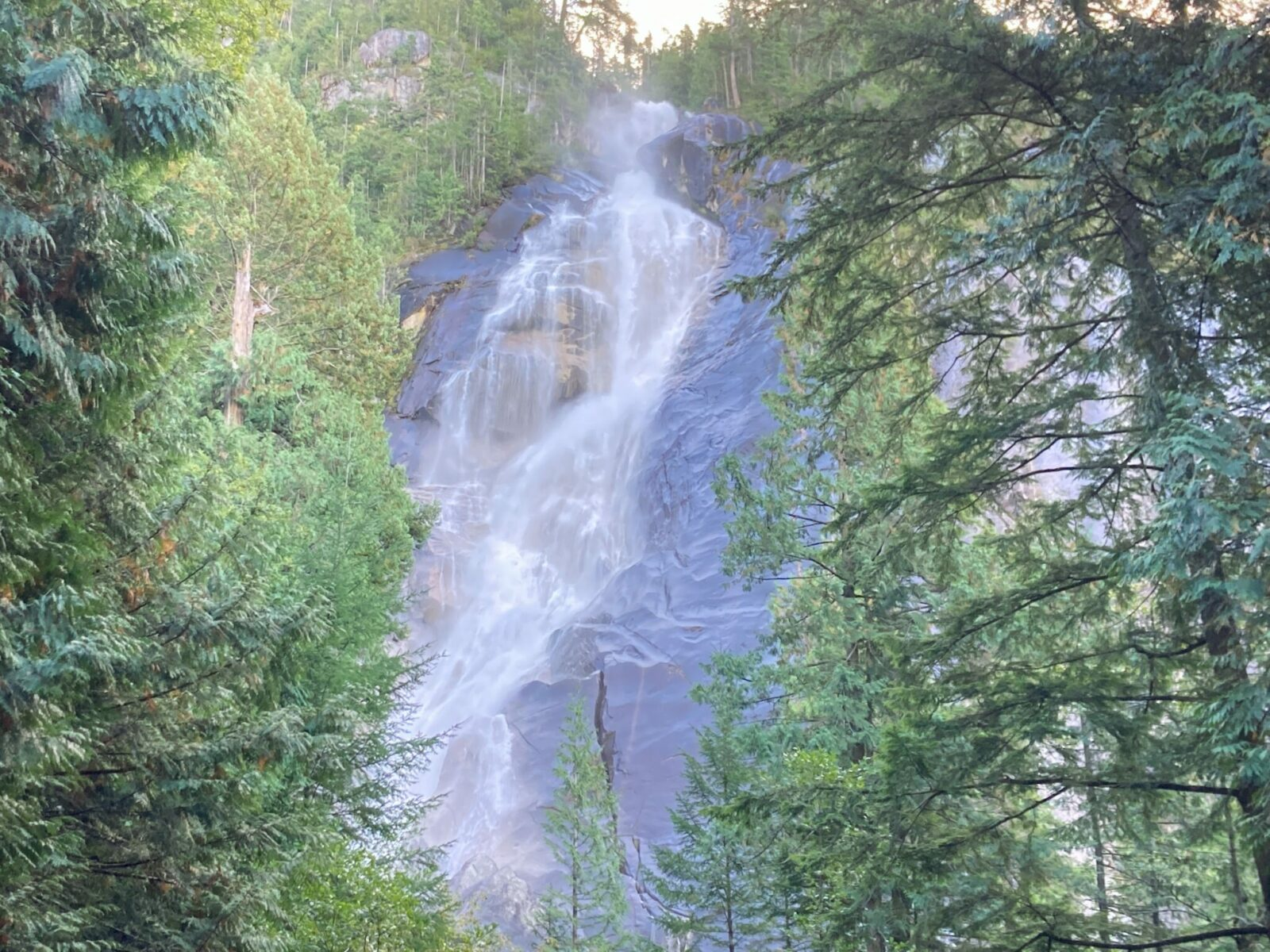 A high waterfall crashing down a rock face in the forest