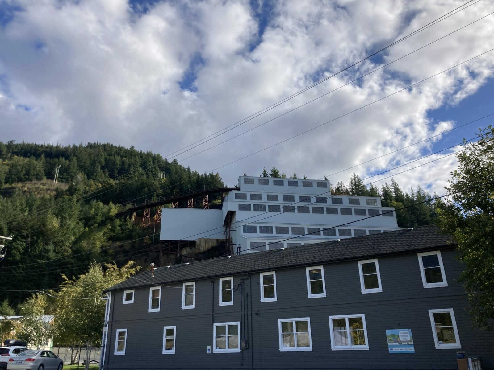 A gray 12 story building connected to the side of a mountain with historic mining trestles at the Britannia Mining Museum along the Vancouver to Whistler drive.