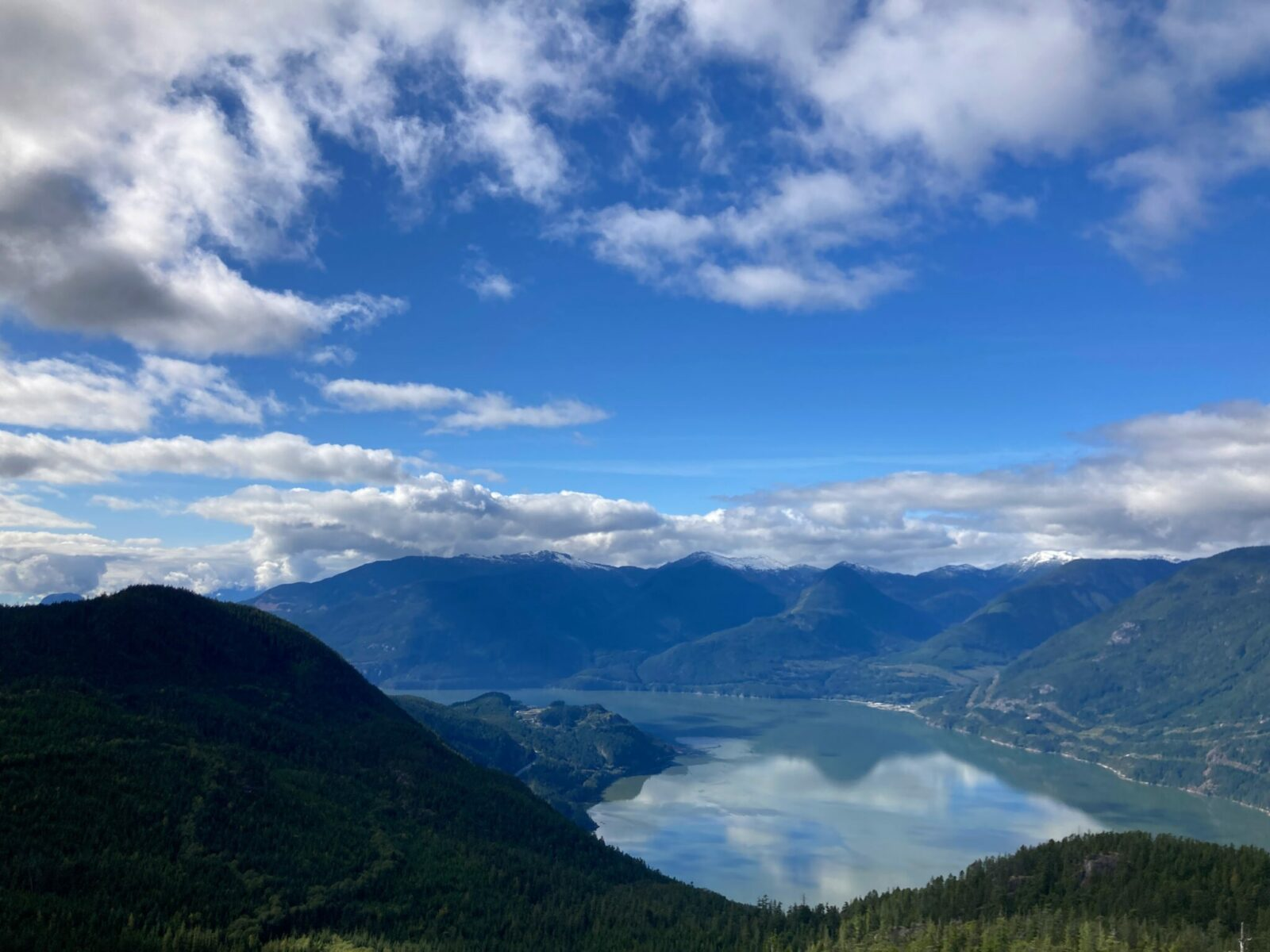 View from the top of the Sea to Sky Gondola on the Vancouver to Whistler drive. It's a partly cloudy day and there are near and distant mountains with a fjord and forests below