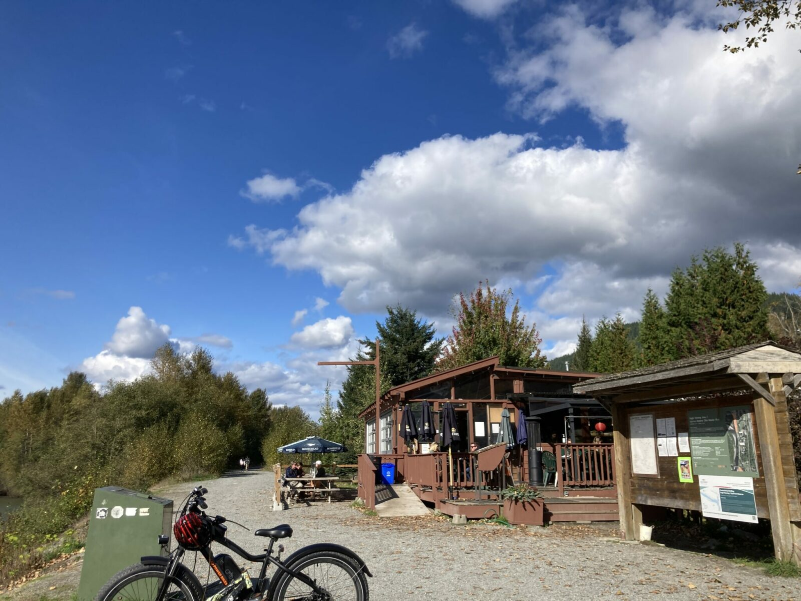 A brown wooden restaurant with a small outdoor deck. There is also a picnic table with an umbrella in front of the restaurant. A gravel path goes across the front and there is a green dumpster and a bike next to the trail. There is also a trailhead sign and forest surrounedin
